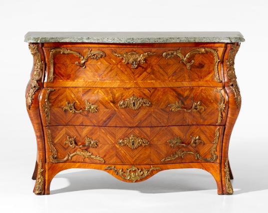 """En högklassig byrå i rokoko av Christian Linning som var mästare i Stockholm 1744-1779. Den vackra möbeln är fanerad med amarant, jakaranda och valnöt och är """"beklädd"""" med förgyllda beslag. Den vackert arbetade skivan är huggen av kolmårdsmarmor och bär en märkning med möbelmästarens efternamn. Utrop är 200 000-250 000 kronor"""