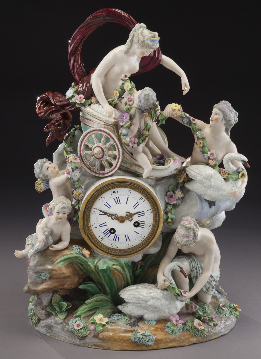 "Meissen porcelain cased mantel clock depicting classical nudes atop a chariot with swans, putti and floral garlands. 20""H, est. - $2,000 - $3,000"