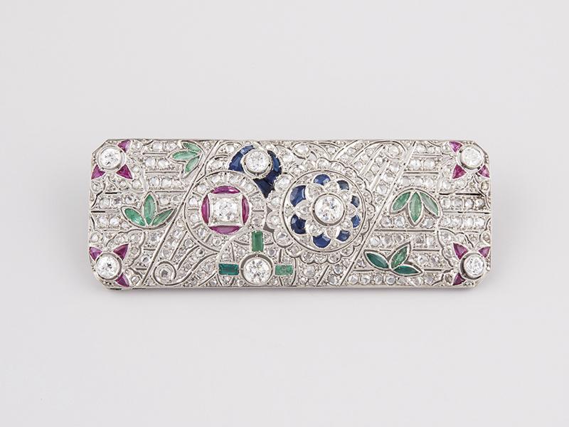 Art Déco-Brosche aus Platin mit Brillanten, Rubinen, Smaragden, Saphiren und Diamanten Ausruf: 2.900 EUR