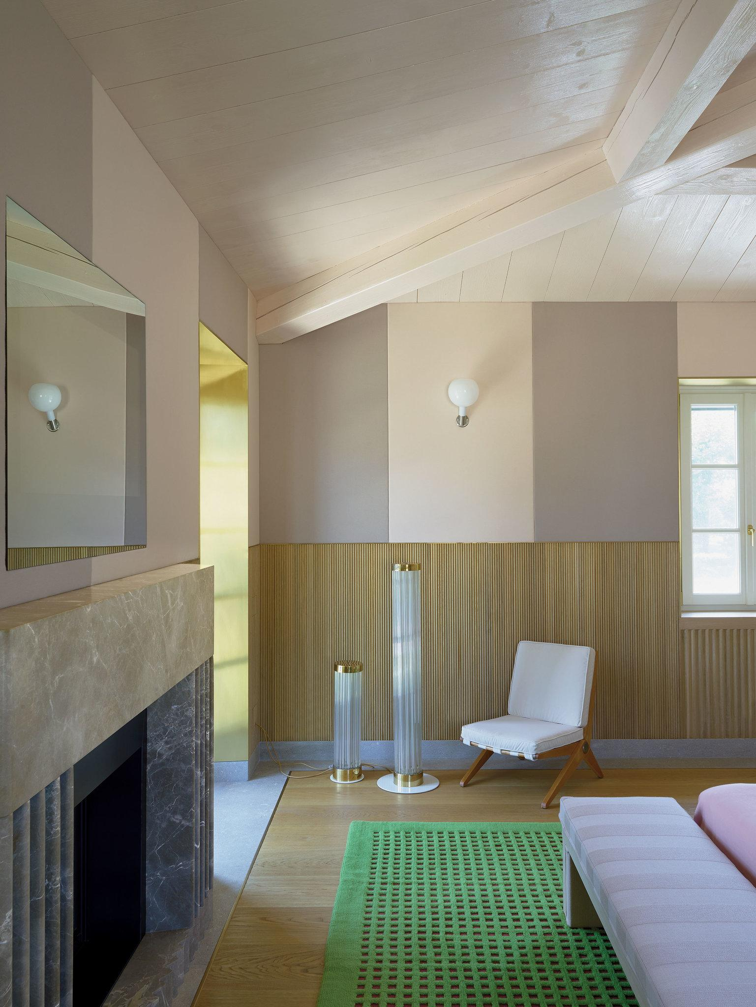 I det stora sovrummet finns en öppen spis i marmor, stolarna är designade av Pierre Jeanneret för Knoll 1952, tyger från Kvadrat, matta av Cogolin och lampor från Morentz gallery. Foto: Henry Bourne