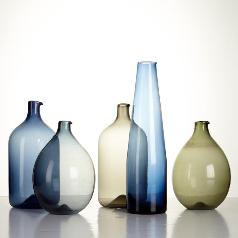 """Timo Sarpanevas flaskor kallas """"i-linjen"""" och har tillverkats för finska glasbruket Iittala. i Föremålen varierar i blå, grå och grön glasmassa och varierar i storlek från 16 till 26 centimeter"""