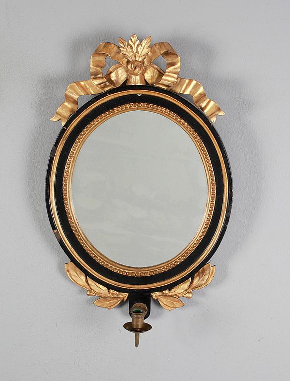 Spegellampett. Gustaviansk, 1700-tal. Målad och bronserad. Oval form. Krönt av bandrosett. För ett ljus. 60 x 40 cm. Utrop: 8.000 sek. Bukowskis market