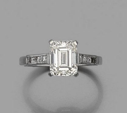 Bague en or gris 18k (750) sertie d'un diamant rectangulaire à pans épaulé de huit diamants calibrés. Estimation basse: 10 000 €