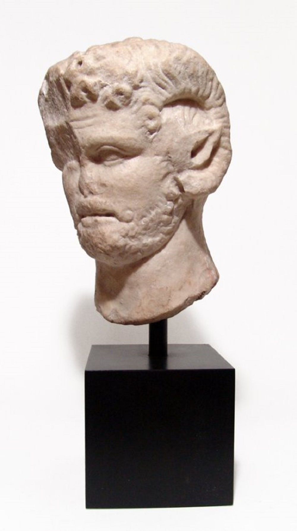 Graeco-Roman marble head of a satyr, with attributes of Zeus-Ammon, circa 1st or 2nd century AD, 9 inches tall and mounted on a heavy square base (est. $18,000-$25,000).