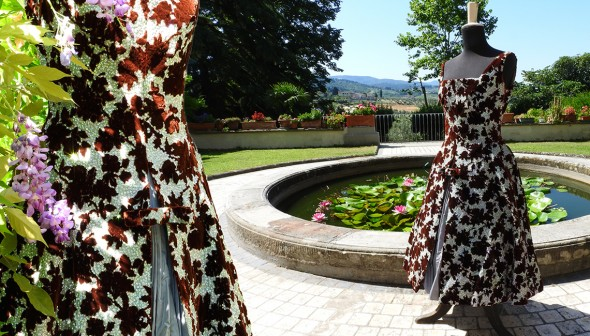 Silbernes Seidenkleid mit Petticoat und weinroten Samtblumen. Foto im Park der Villa in Chianti aufgenommen.