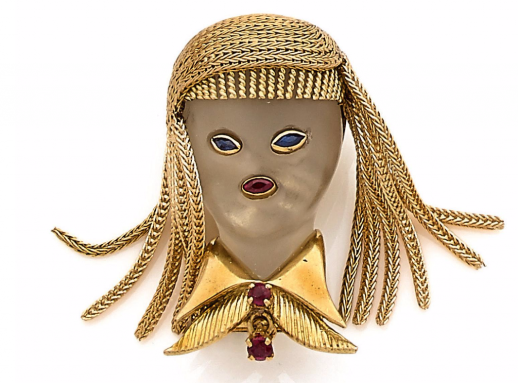 """Van Cleef & Arpels, Clip """"femme"""" en or jaune et cristal de roche poli pour le visage rehaussé de saphirs et rubis pour les yeux, la bouche et le col, Vers 1950"""