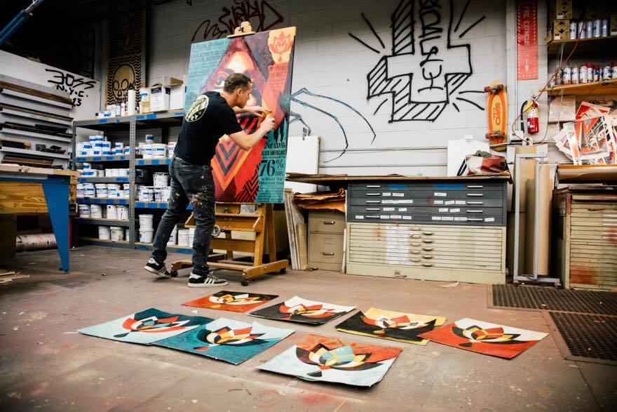 Shepard Fairey travaillant sur une pièce de l'exposition «Damaged»