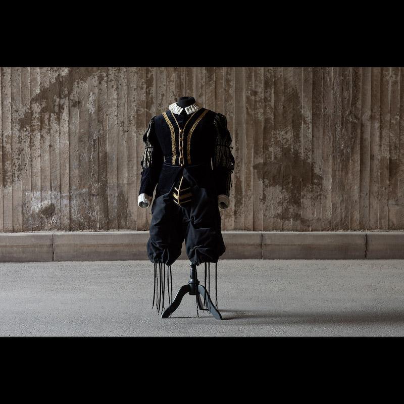 Operan Rigoletto hade premiär den 12 september 1987 på Kungliga Operan. Design Agneta Skarp och regi Georg Malvius. Svart jacka och byxor med gulddetaljer. Storlek large.