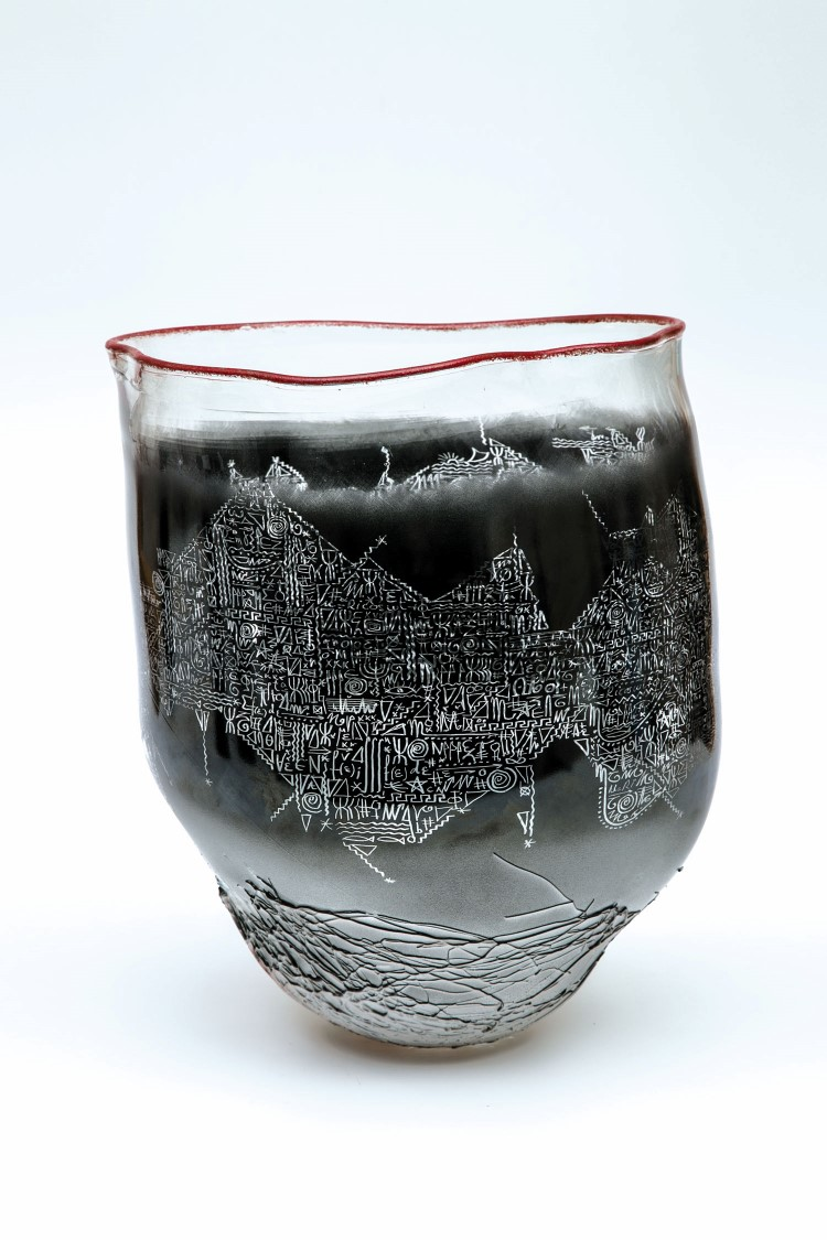 Großes Vasenobjekt. Farbloses Glas mit aufgesprühter schwarzer und hellrosa Emailfarbe. Umlaufend geritzter Dekor und Inschrift. Auf der unteren Wandung plastische Fadenaufschmelzung. Lippenrand mit roter Emailfarbe. Mündungskontur mit roter Emailfarbe. Auf der Wandung bez.: J.P. Umbdenstock 1991. H. 38 cm Lit.: Contemporary European Sculptures in Crystal and Glass (1987-1989), Ausst.-Kat., Liège 1989, Abb. 21. Niedrigster Katalogpreis: 1500 EUR