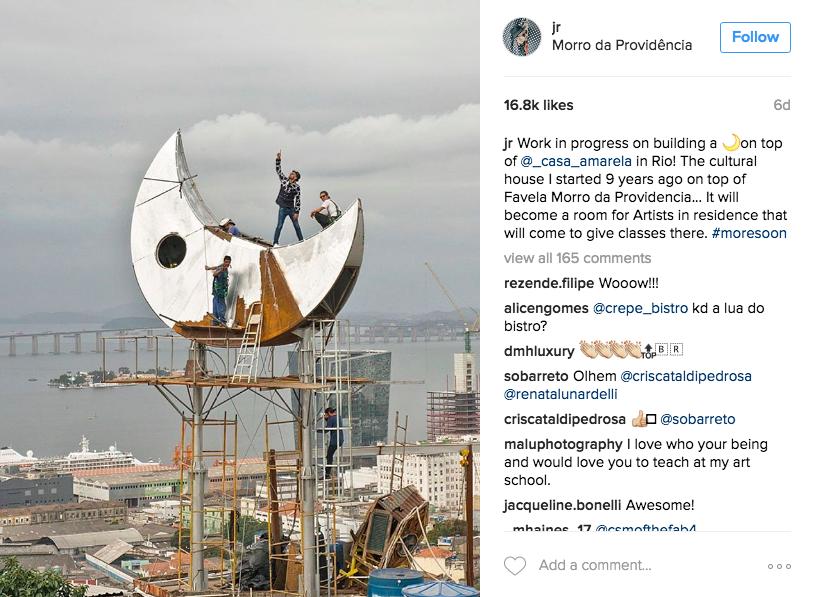JR, jamais sans son chapeau et ses lunettes noires, sur sa 3è installation de Rio Image: Instagram de JR