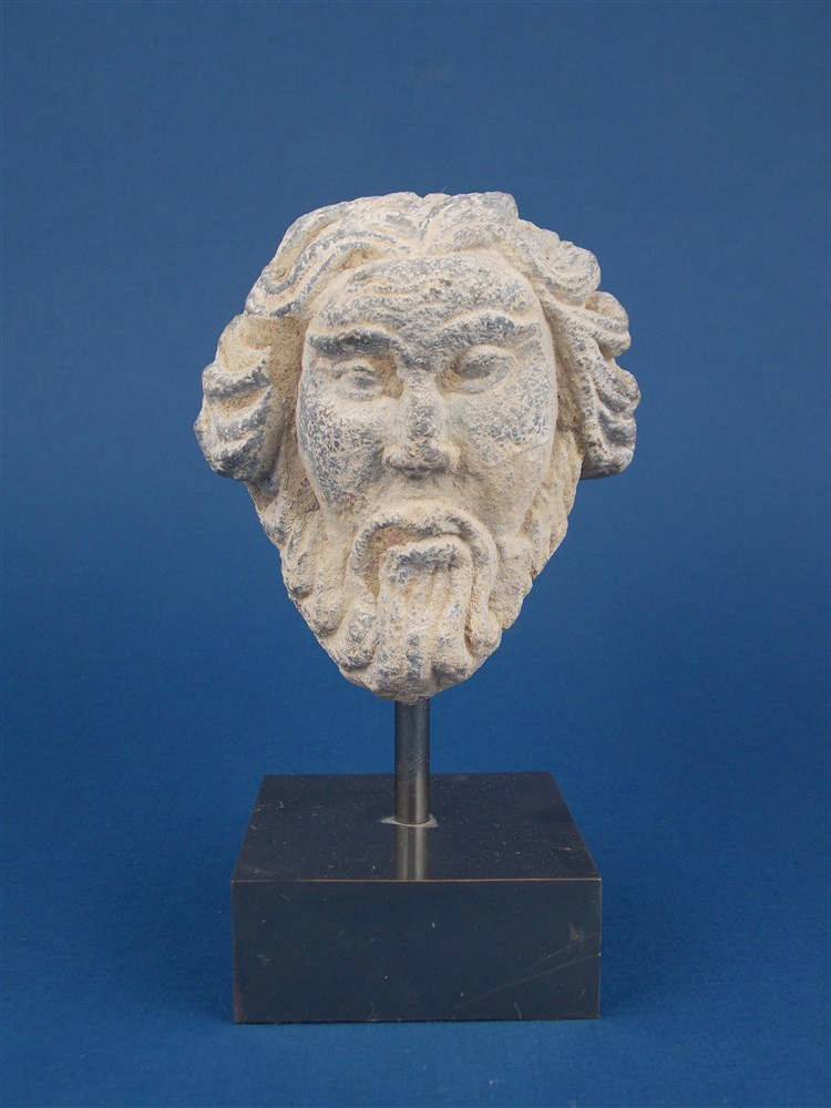 A bearded head of shale carved with metal base (Gandhara) from the fourth century AD, with a document of origin, from a former private collection in London, acquired around 1980.