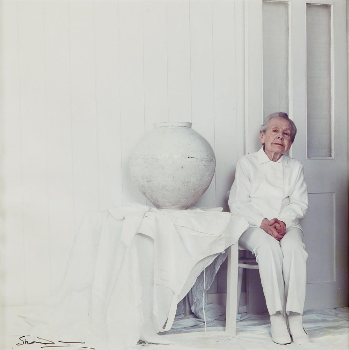 ANTONY ARMSTRONG JONES. Fotografía de Lucie Rie sentada junto a una vasija coreana (c. 1990). Imagen vía: Phillips