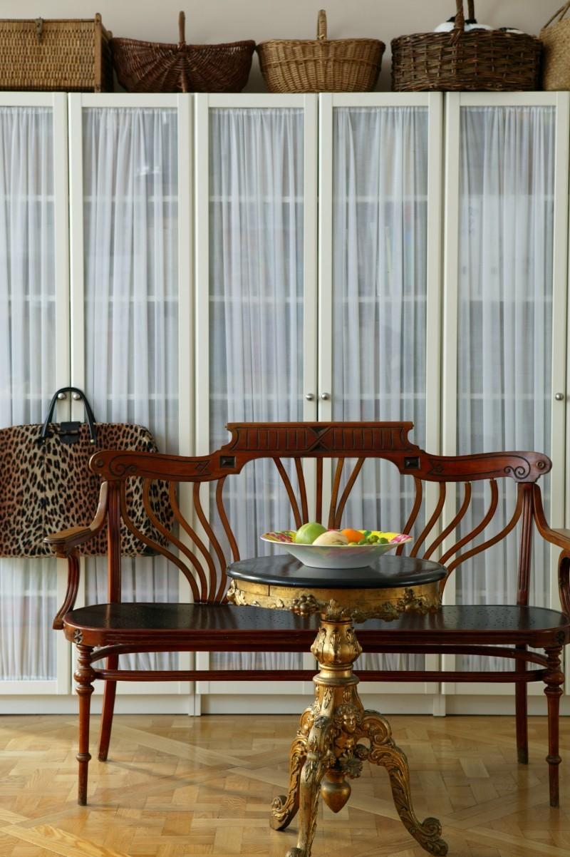 Un canapé et un plateau de style Art Nouveau orné d'ornements baroques devant l'étagère Billy d'IKEA