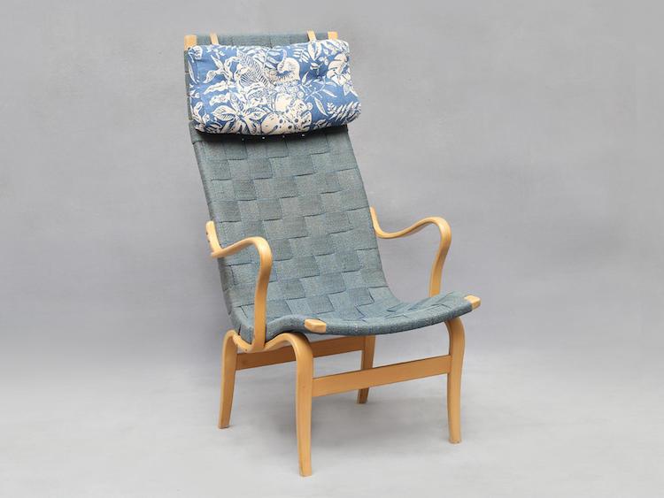 """Fåtölj """"Eva Hög"""". Bruno Mathson för firma Karl Mathson daterad 1965, blå originalklädsel i sadelgjord och nackkudde, skiktlimmad bok, dubbla brännstämplar (klädseln något blekt). Utrop: 2 500 SEK. Auktionskammaren i Vätterbygden"""
