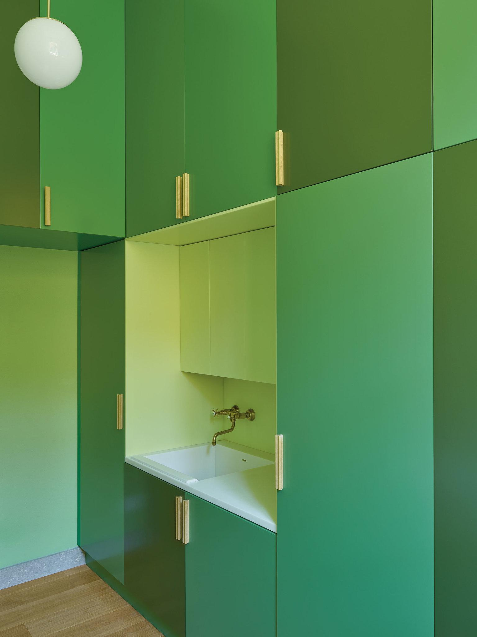Opaque lacquered cabinets in shades of green in the laundry room