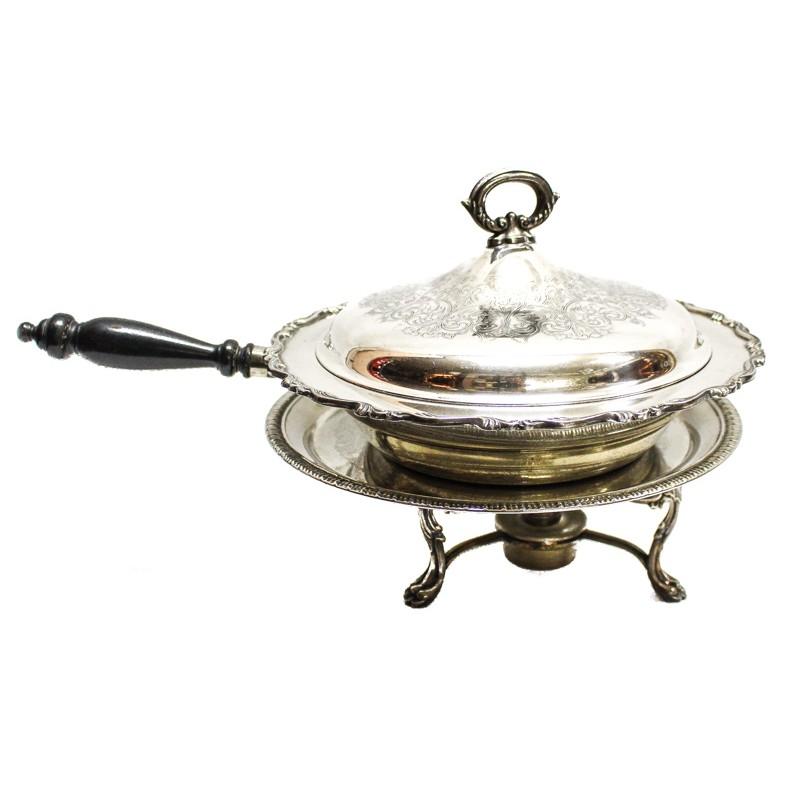 Legumbrera en metal plateado con profusa decoración cincelada y calentador