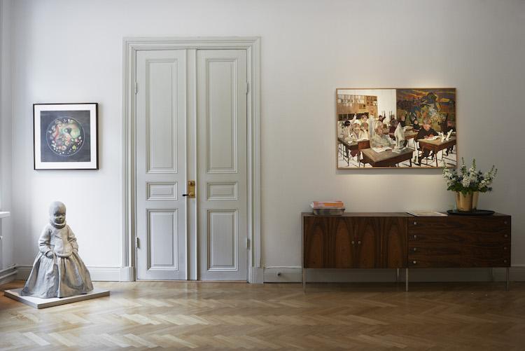 """Över sidboardet hänger favoritmålningen """"Klassrum"""" av Karin Mamma Andersson."""