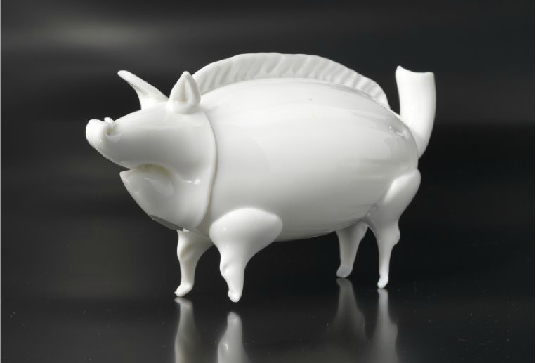 Fyllesvin. Troligtvis Gjøvik. Benvitt glas. Formad som ett vildsvin, med stark rygg byst. 1800-tal. Blomqvist.