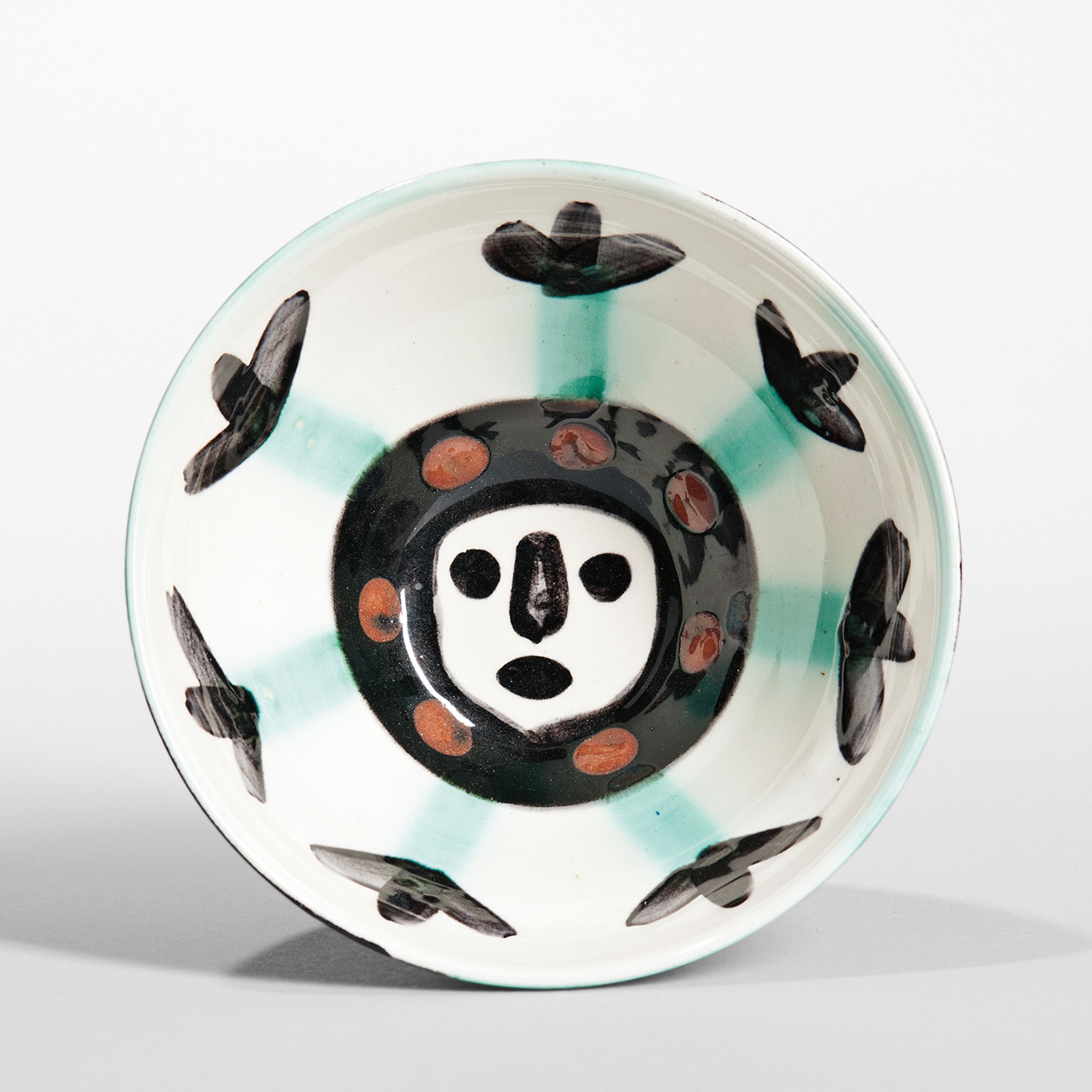 Pablo Picasso (1881-1973) Visage Bowl Glazed ceramic 1955 Madoura round cup of white clay hand-decorated in engobes, black, green, and brick red underglaze, marked Edition Picasso Madoura, ht. 2 1/2, dia. 5 1/8 in.