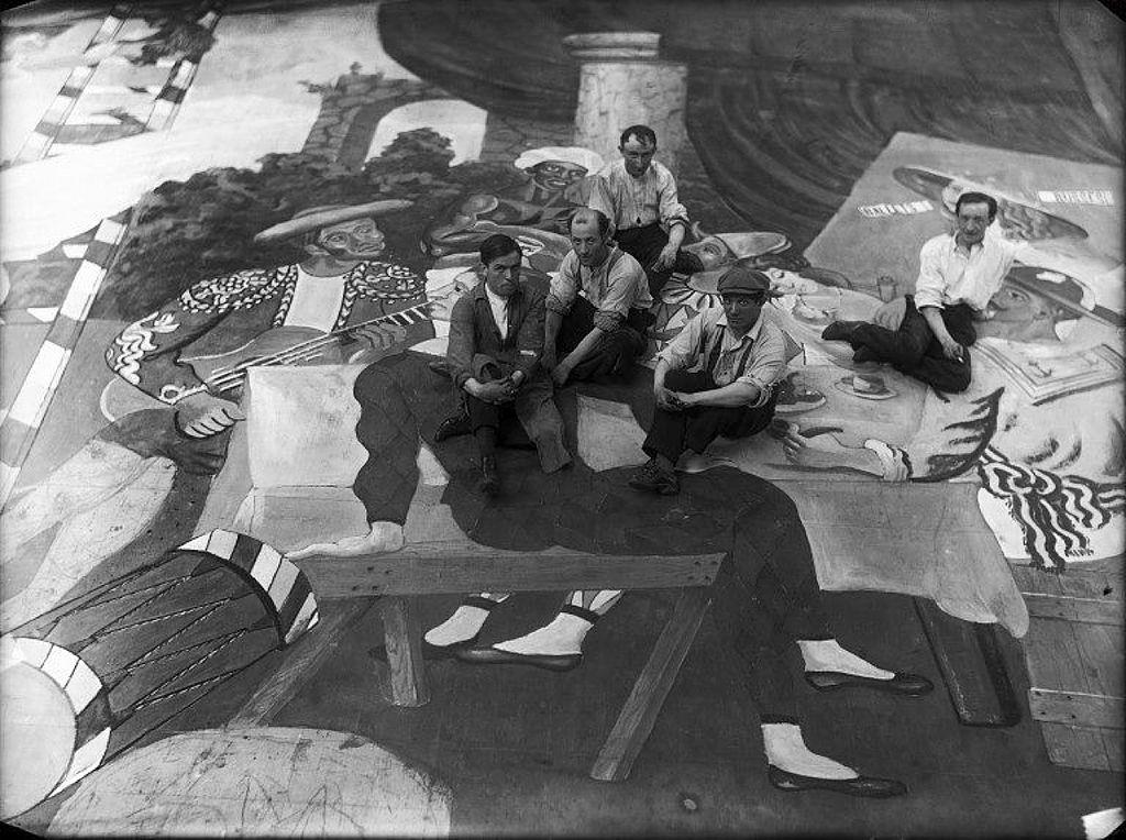 """Pablo Picasso (näst längst till höger, i keps) omgiven av scenarbetare inför uppsättningen av balettet """"Parade"""". circondato da operai scenici durante i preparativ. Foto via Wikimedia Commons."""