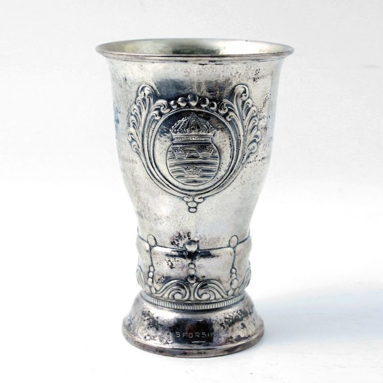 Nr 933 1105. Bägare. Silver, Danmark, 1934, Heimbürger, Reliefdekor med Trekronor emblem, graverad, tillverkare SJ, höjd: 20, 430g ca. Utropspris: 4 000 SEK.