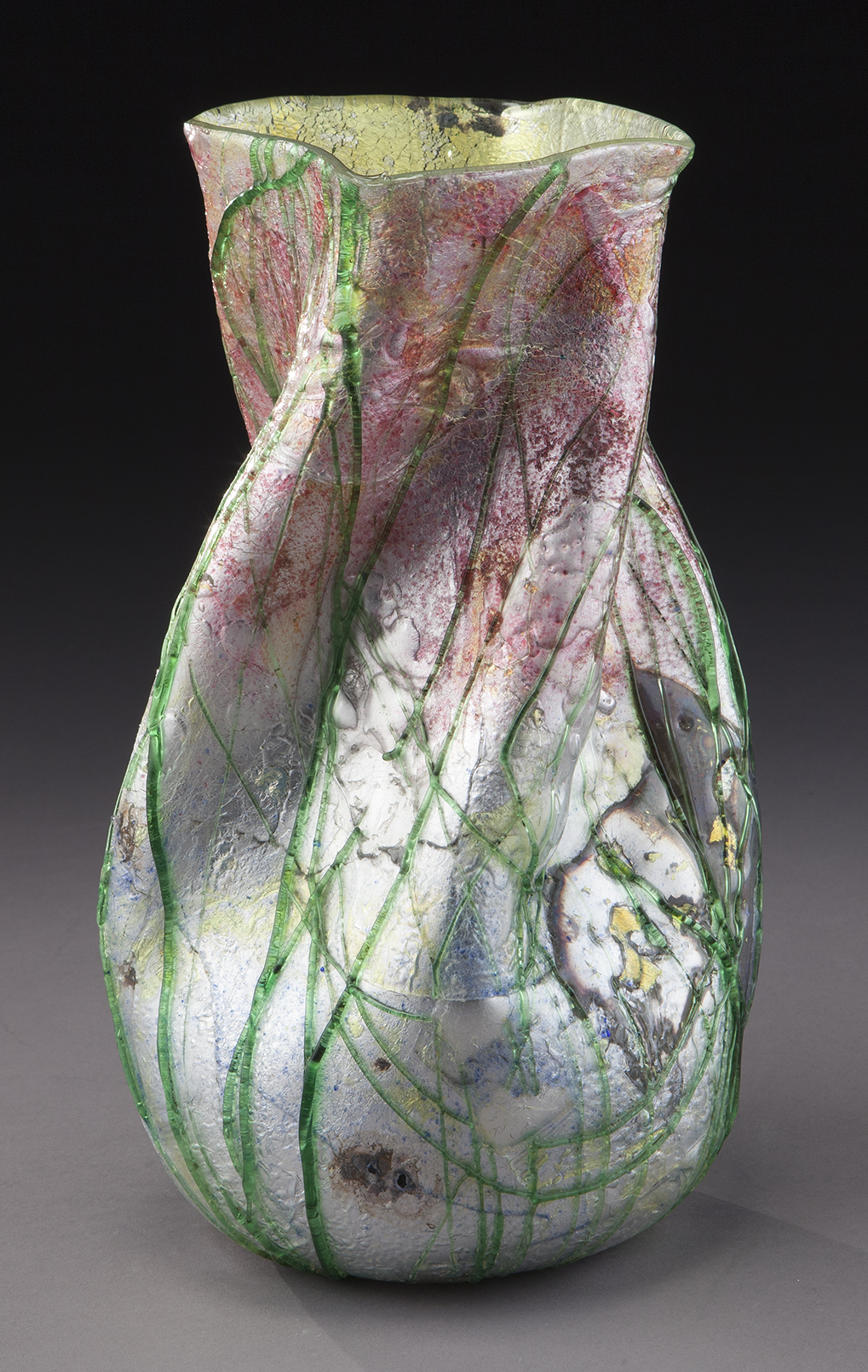 """Steven & Williams silveria glass vase, twist form with applied green threading over silver platinum and rose ground. With Stevens and Williams Fleur-de-lis signature. 11.25""""H, Circa - 1920."""