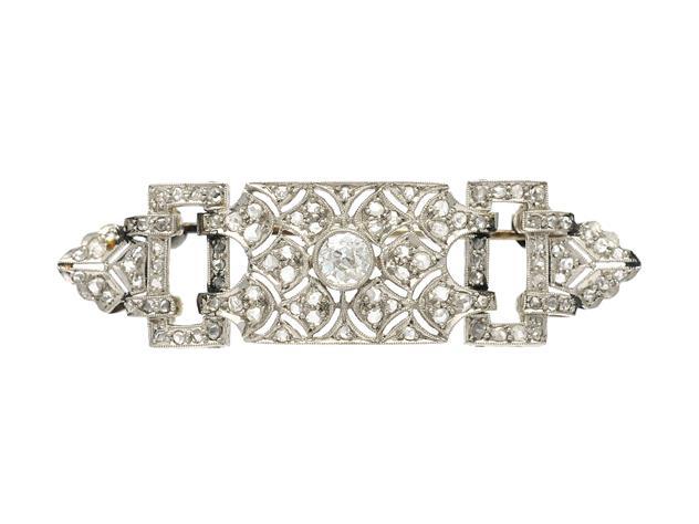 BROSCH, platina, med nålfäste i 18K vitguld, gammalslipad diamant ca 0,30 ct, ca W(H)/VS, rosenslipade diamanter ca 0,45 ctv, 1900-talets första hälft, längd 5 cm, vikt 9,3 g, nagg på mittstenen, i övrigt nagg på ett fåtal av rosenstenarna. Utropspris: 6 200 SEK.