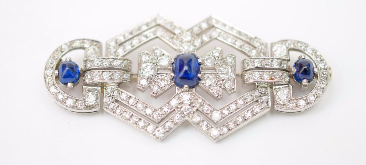 Broche en platine composée de motifs géométriques imbriqués, ornée de trois saphirs cabochons, entièrement sertie de diamants de taille ancienne, agrémentée de roses, années 1930