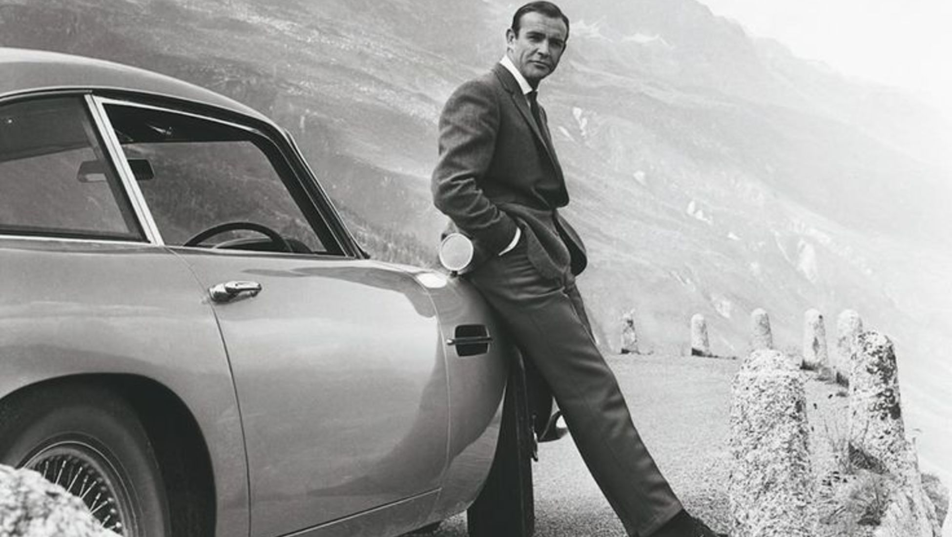 "Actor Sean Connery poses as James Bond next to his Aston Martin DB5 for movie 'Goldfinger"", 1964 - Photo by Donaldson Collection - Michael Ochs Archives via Barneby.fr"