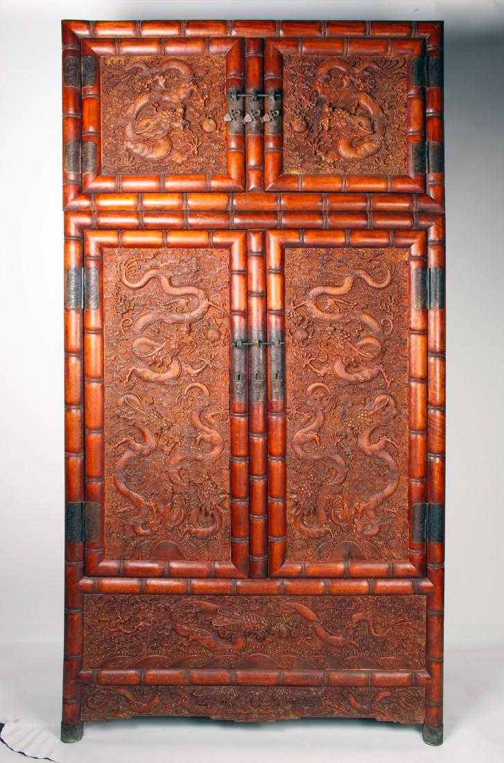 Elaborately carved huanghuali cabinet with dragons and a flaming pearl carved on all front facing surfaces and one side, 94 inches tall (est. $5,000-$8,000).
