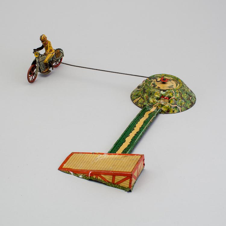 Den urverksdrivna motorcykeln i litograferad plåt med hoppbana i är tillverkad för Huki i Tyskland på 1930-talet. Utropet är 5 000 kronor