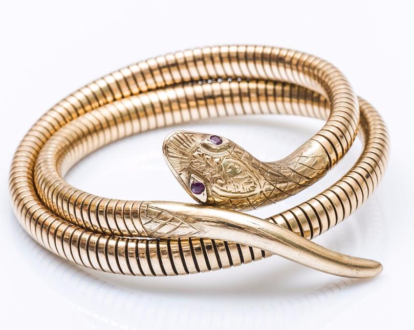 Bracelet serpent tubogaz en or jaune 9 carats (375 millièmes), la tête ornée d'un décor ciselé, les yeux sertis de petits rubis Pestel-Debord