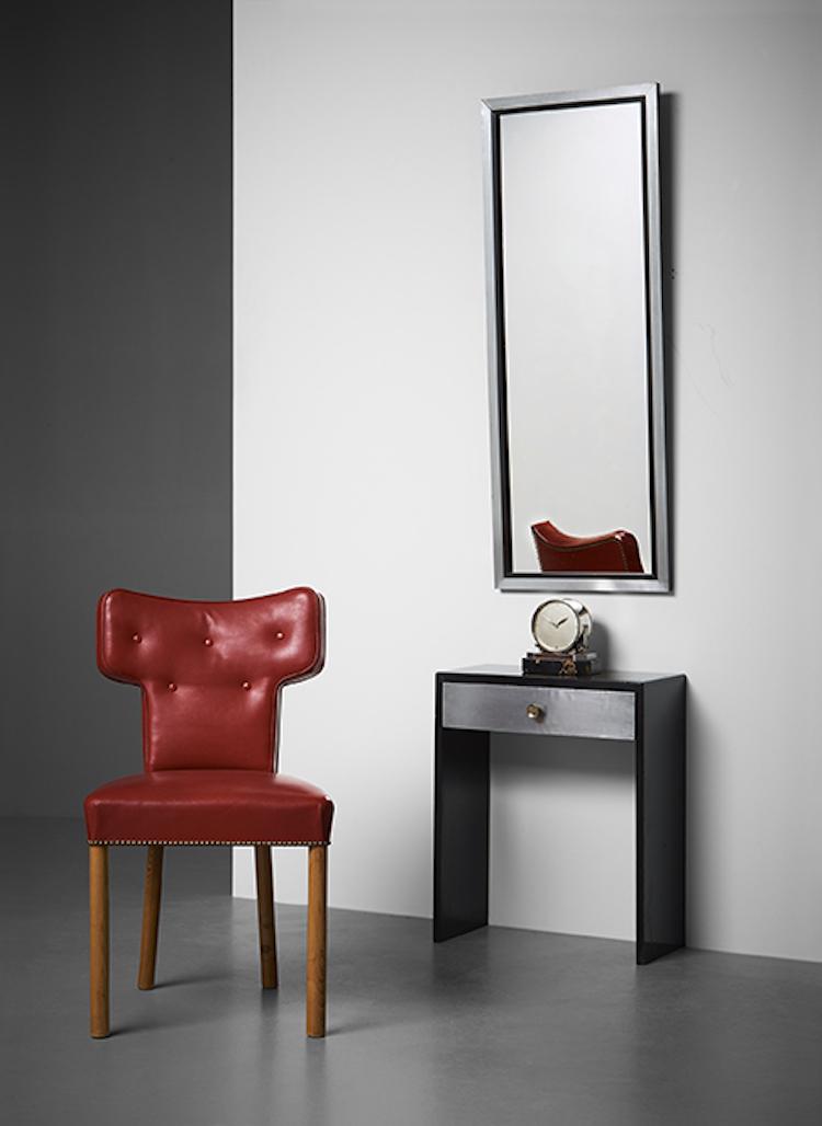 Den röda skinnklädda stolen av Uno Åhrén är i exceptionellt bra skick. Utrop 50-70 000 kronor på Bukowskis. Spegeln och den enlådiga byrån från 1930-talet är av anonym formgivare. Utropet är 20-25 000 kronor.