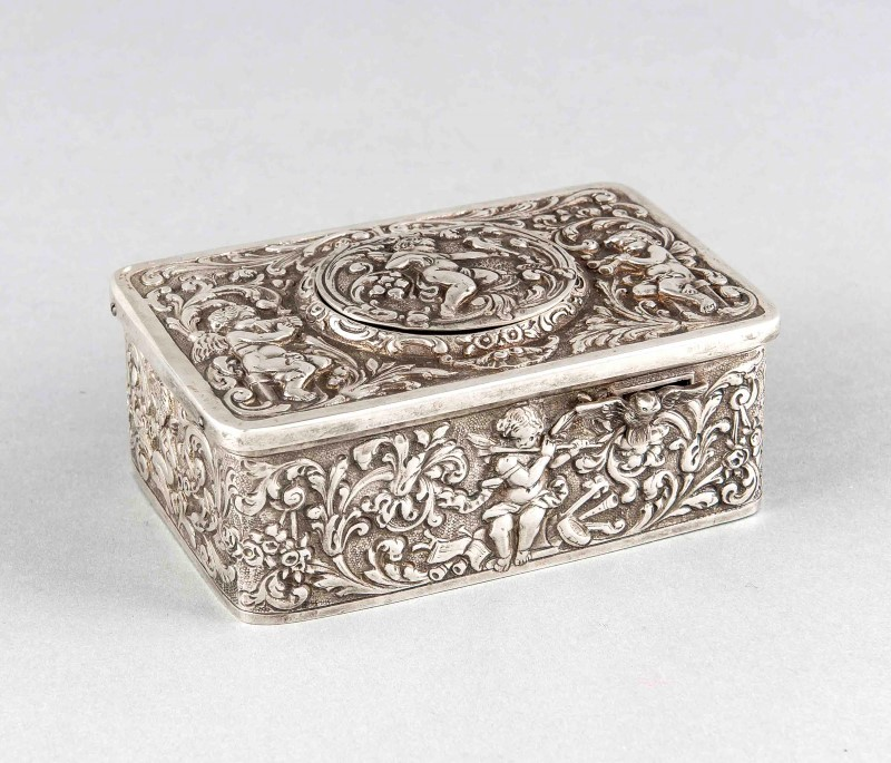 Music box with songbird, Germany, circa 1920, J. Kurz & Co., Hanau, sterling silver 925/000, rectangular case with rich relief decorations, floral and putto motifs, front includes sliding mechanism, cover with spring lid, including mechanically moving bird, functional, with a beautiful voice, sawn out cartridge, complete with key, 4 x 10 x 6.5 cm, gross weight about 538g. Estimate: $2,000