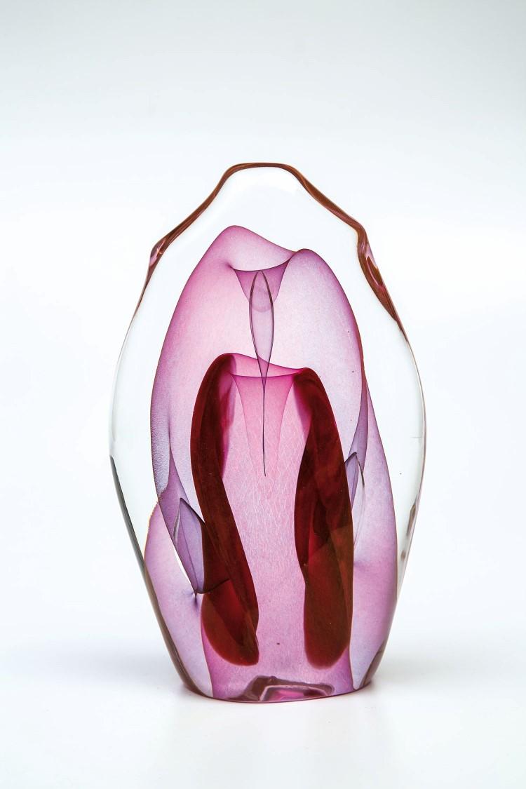 Farbloses Glas, mehrfach rosa überfangen, eingearbeitete Luftblasen, Hütteniris, Klarglasüberfang. In Vibrogravur bez.: Labino 3-1978. H. 20 cm. Niedrigster Katalogpreis: 2500 EUR. Dominick Labino (1910 - 1987) zählt neben Erwin Eisch und Harvey K. Littleton zu den Mitbegründern der Studioglasbewegung. 1963 begann er mit heißem, geblasenem Glas als künstlerischem Medium zu arbeiten. Er entwarf und baute seine eigenen Schmelzöfen, Kühlöfen, Glasbläserwerkzeuge und Einrichtungen zur kalten Endbearbeitung. Sein umfangreiches Werk ist in 65 Museen der Vereinigten Staaten sowie im Ausland vertreten.