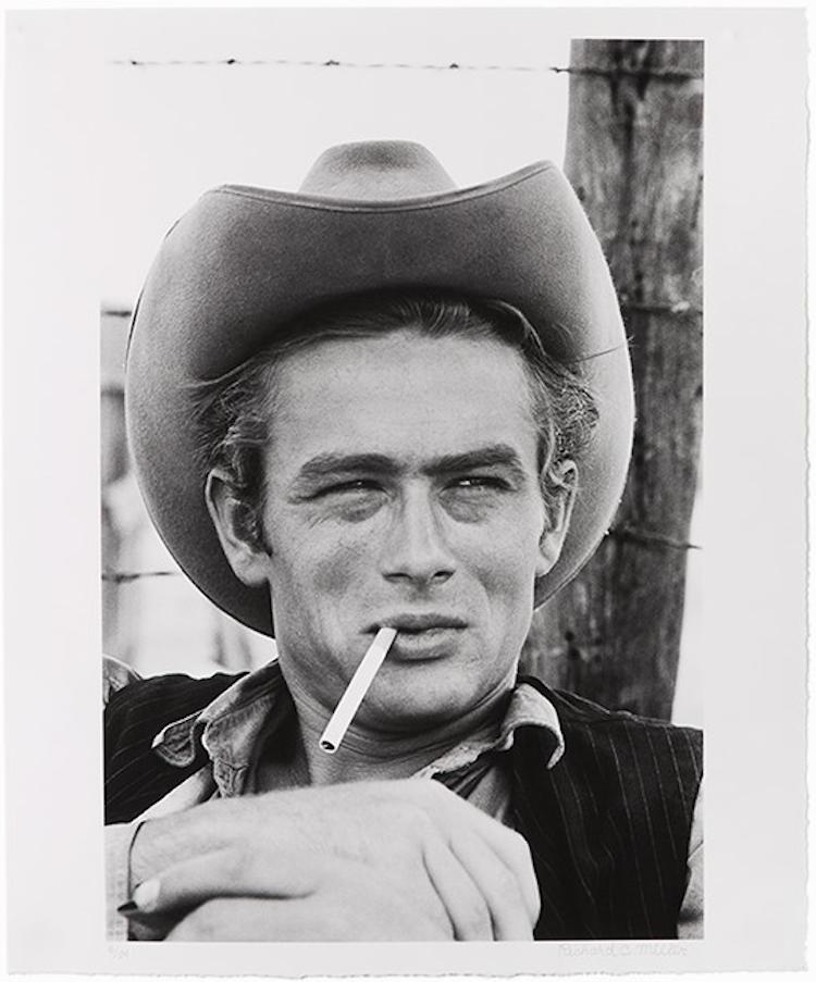 """Richard C. Miller är mest känd för sina """"bakom-kulisserna""""-fotografier. Hans första uppdrag var under inspelningen av filmen """"Giant"""" och det var även här Miller träffade den numera kulturella ikonen, James Dean. Detta fotografi av Dean visar skådespelaren liggandes framför ett staket med en cigarett dinglandes från hans mun, fullständigt avslappnad framför kameran. """"Giant"""" var Deans sista film innan hans tragiska dödsfall, som inträffade innan filmen släpptes. Dean fick sin andra Oscarsnominering för hans gestaltande av Jeff Rink. Utropspris 28 100 SEK."""