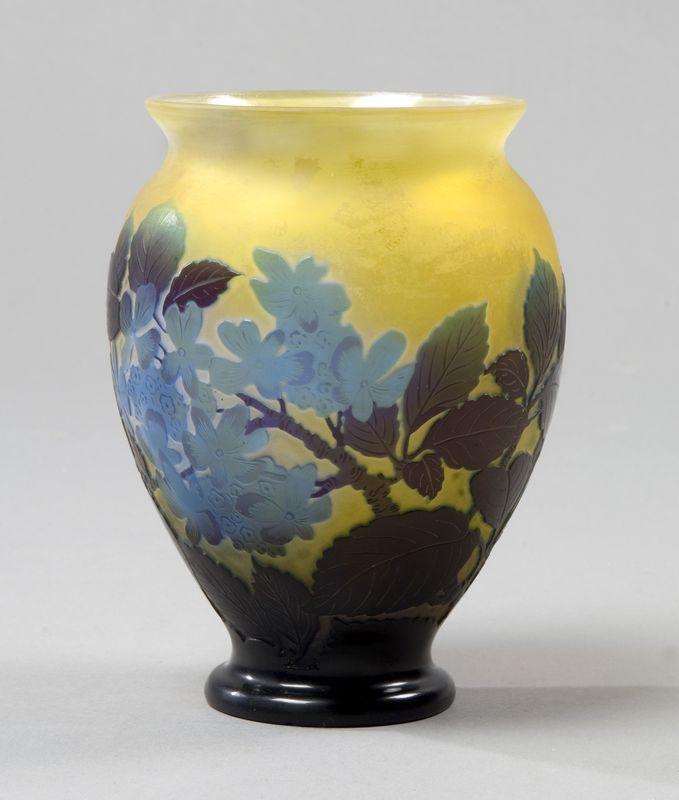 Gallé - Vase sur piédouche en verre soufflé à fond jaune à décor dégagé à l'acide en violine de branchages fleuris. Signature en creux dans le décor.