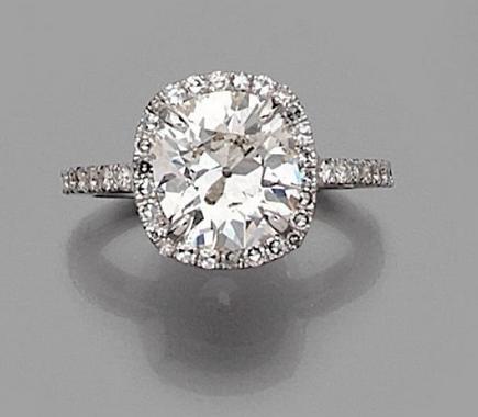 Bague en or gris 18k (750) ornée d'un diamant coussin entouré et épaulé de diamants taillés en 8/8. Estimation basse: 30 000 €