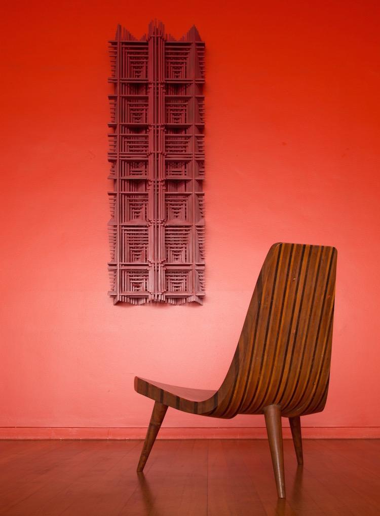 """Joaquim Tenreiros stol """"Chaise tripode"""" från 1947 av olika exotiska träslag har ett utrop på 120-160 000. På väggen """"Relevo"""" från cirka 1970 med ett utrop på 40-50 000 euro."""