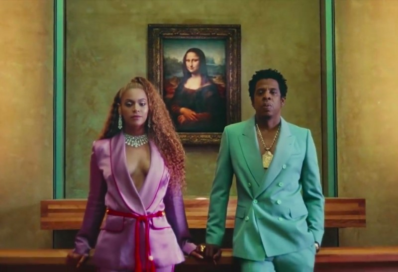 """Still from """"Apeshit"""" – the couple posing in front of the Mona Lisa in 2018. Photo via: NY Times."""