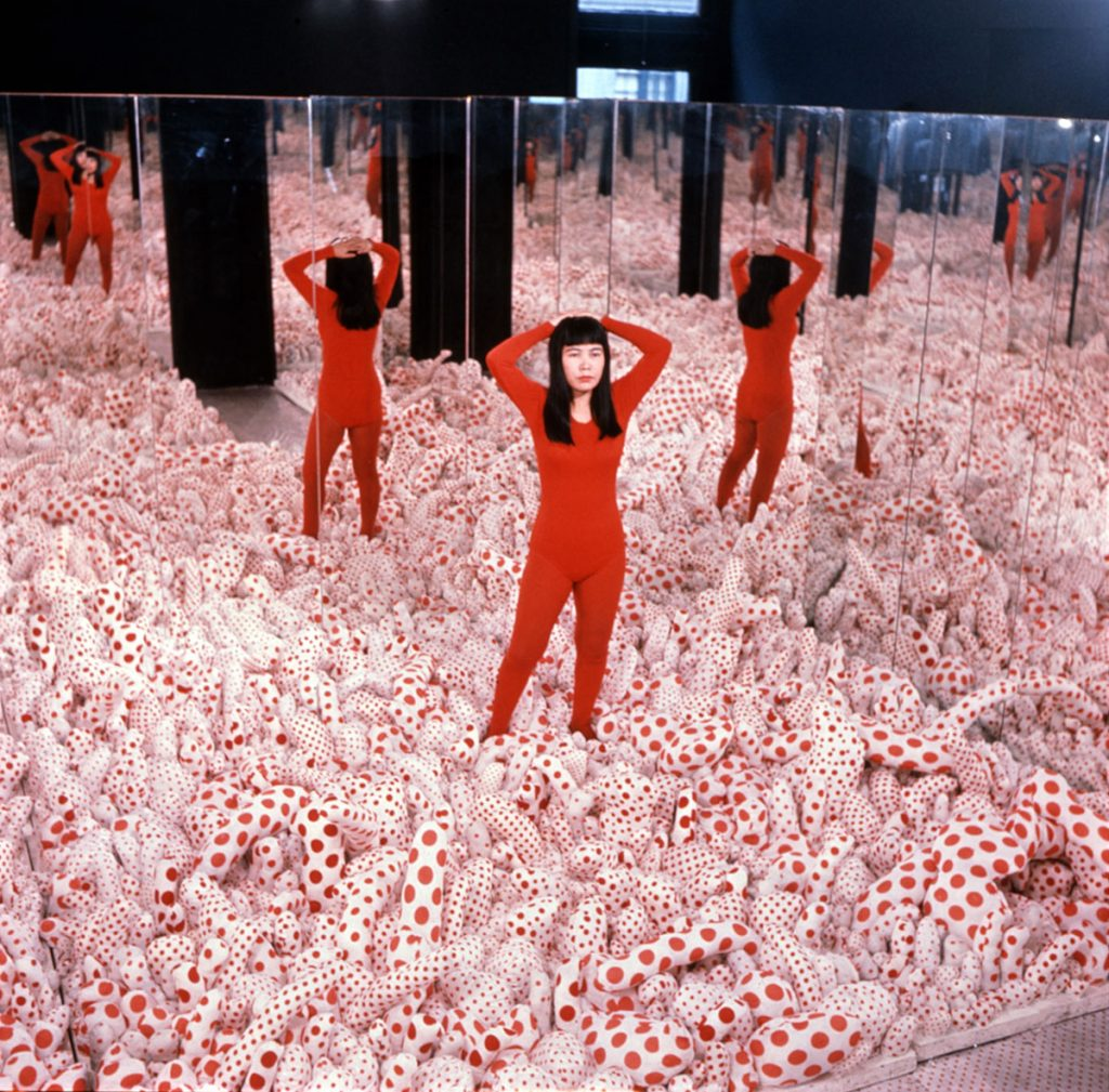 Yayoi Kusama debout dans son installation Phalli's Field, 1965