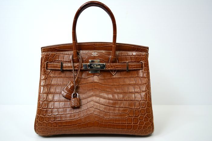 Bolso HERMÈS, modelo Birkin 30 en piel de cocodrilo color marrón. Precio estimado: 40.600-52.780 €