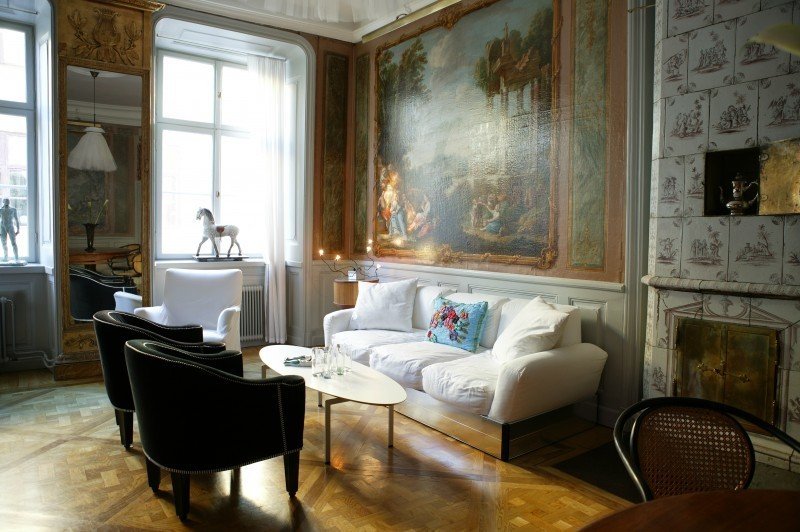 """Une toile """"Hollandaise"""" de la première moitié du 18ème siècle se trouve dans le salon avec des carreaux peints à la main. La lampe """"Liv"""" de Jonas Bolin se reflète dans le coin du salon"""