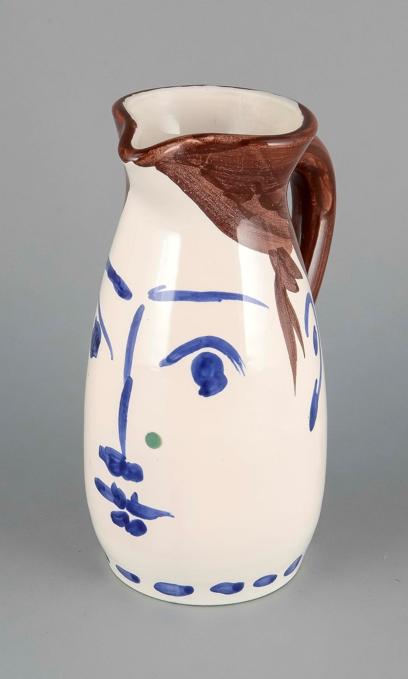 Picasso pitcher 'Visage', Madoura, manufacture stamp, impressed mark 'Edition Picasso' and brush brand 'Edition Picasso 207/300, Madoura' design by Pablo Picasso (Málaga, 1881 - Mougins, 1973) around 1959, lean Henkel jug with white glaze, painted in blue and brown in the shape of a woman's face, h. 22 cm. Limit: 2000 EUR