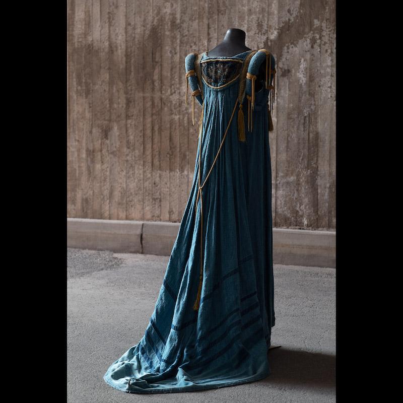 Operan Rigoletto hade premiär den 12 september 1987 på Kungliga Operan. Design Agneta Skarp och regi Georg Malvius. Klänning i blått råsiden med metallbandsbesättningar. Buren av Prinsessan Madeleine 2001 på Kungaparets silverbröllopsfest. Storlek medium. Utrop 4-5 000 kronor