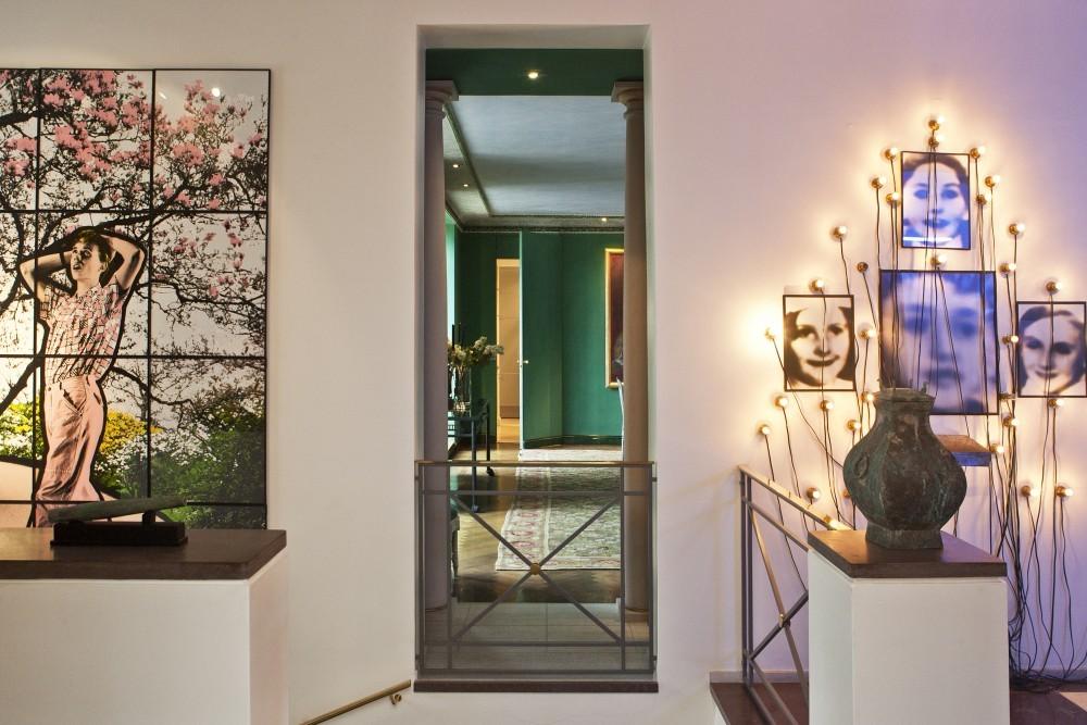 Zwischen zeitgenössischen Kunstwerken gewährt eine Wandöffnung einen Blick in das grüne Esszimmer.