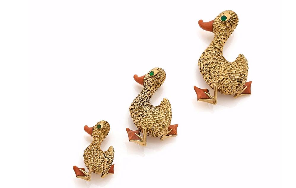 """Van Cleef & Arpels, Ensemble de trois clips """"la famille canard"""" en or jaune ciselé, les palmes et les becs sont ornés de corail, les yeux sont sertis d'un cabochon d'émeraude, Vers 1960"""
