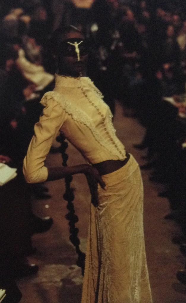 Alexander McQueen i en utmanande pose, i en åtsittande klänning som med inspiration från sekelskiftet.