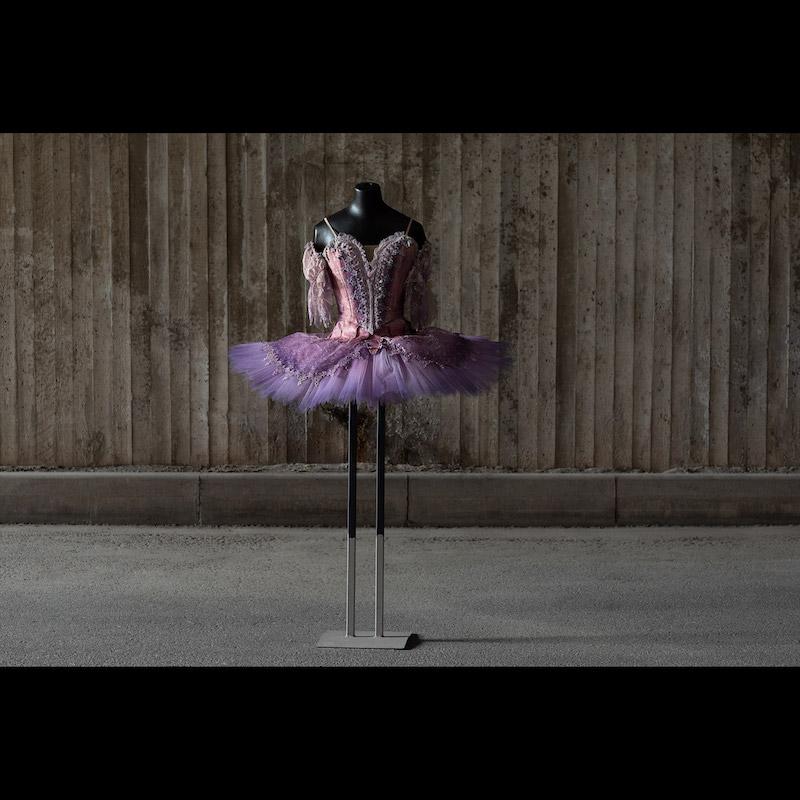 Tutu från baletten Törnrosa som hade premiär den 15 november 1985 på Kungliga Operan. Design David Walker och koreografi Marius Petipa och Beryl Grey. Lila fens tutu med spetsskört och laméliv. Storlek small. Utrop 3-4 000 kronor