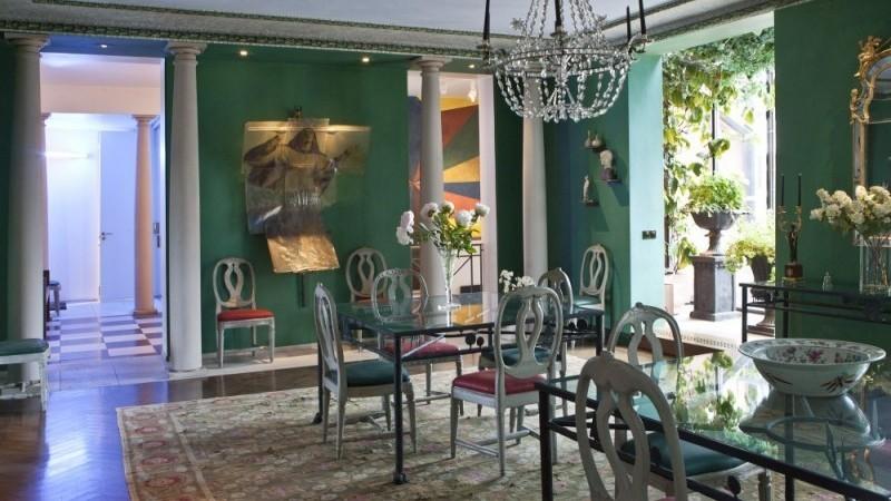 Les colonnes ioniques de l'entrée contrastent avec la couleur des murs. Sous la table, on observe un immense tapis aux couleurs vives